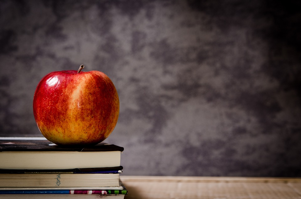 An apple sitting on top of books resting atop a desk.